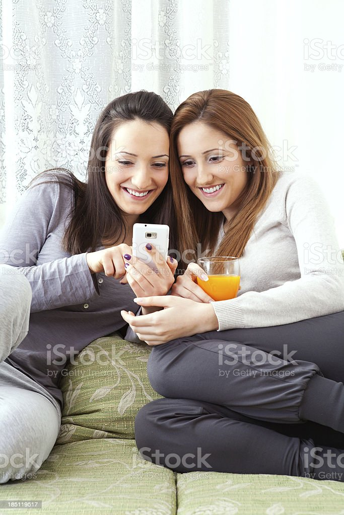 sisters looking mobile phone and smiling royalty-free stock photo