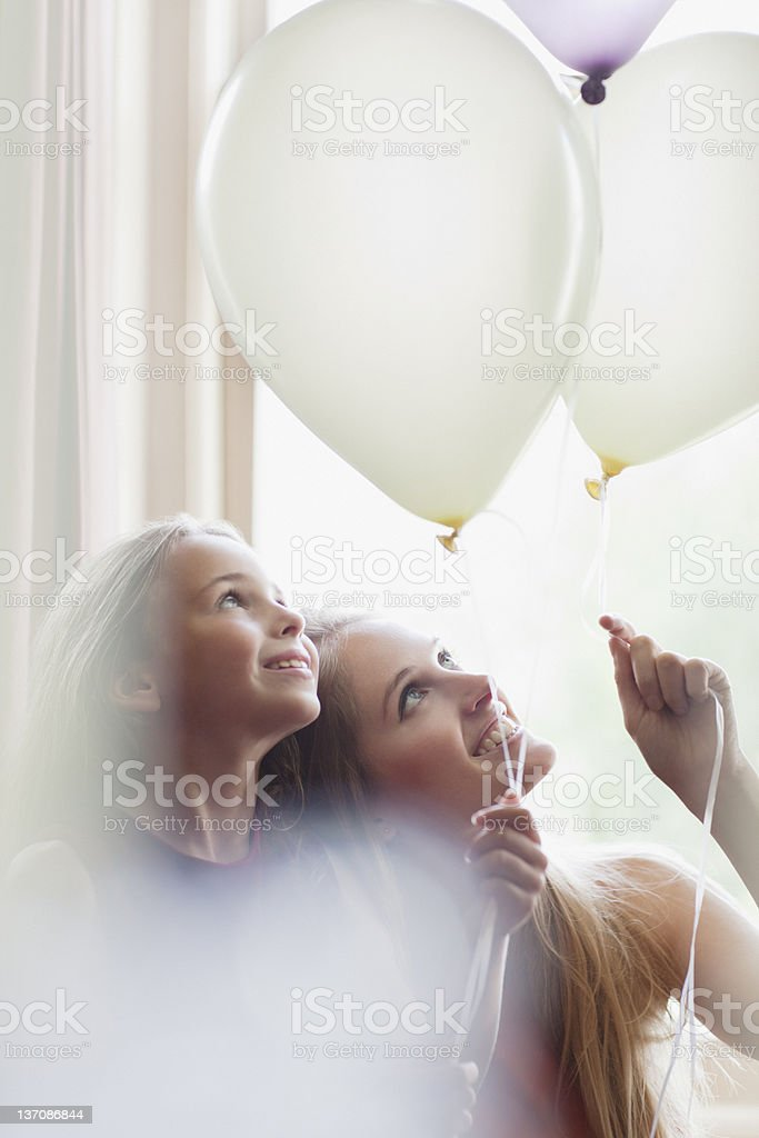 Sisters looking up at white balloons royalty-free stock photo