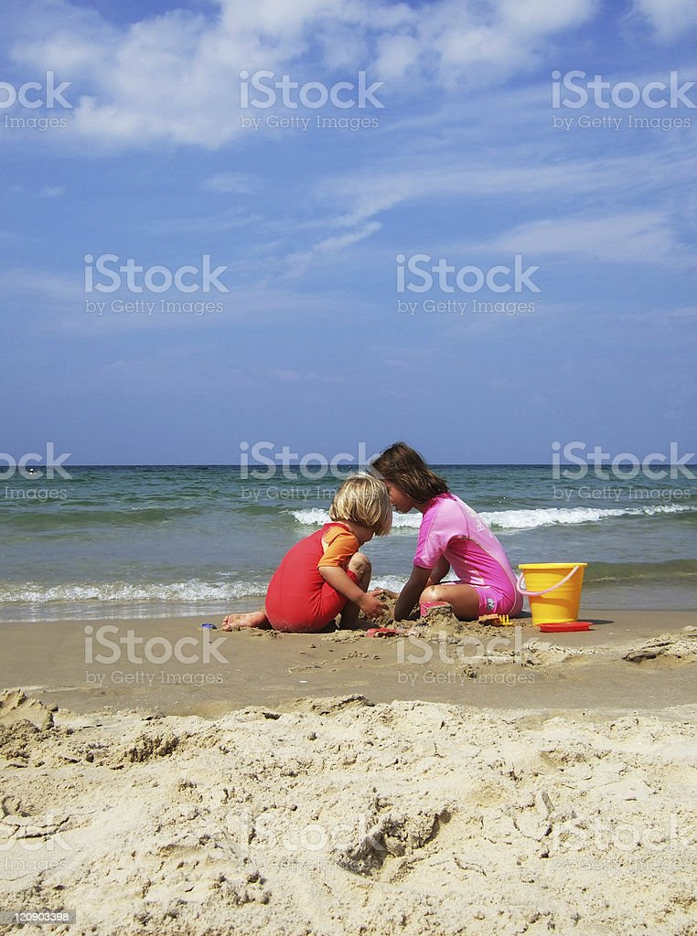 Sisters playing in the sand with beach view stock photo