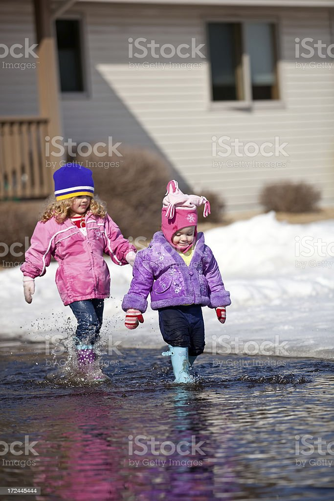 Sisters Playing in Water Puddle royalty-free stock photo