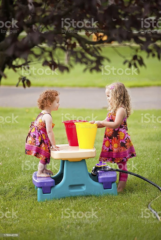 Sisters Playing With Water & Buckets stock photo