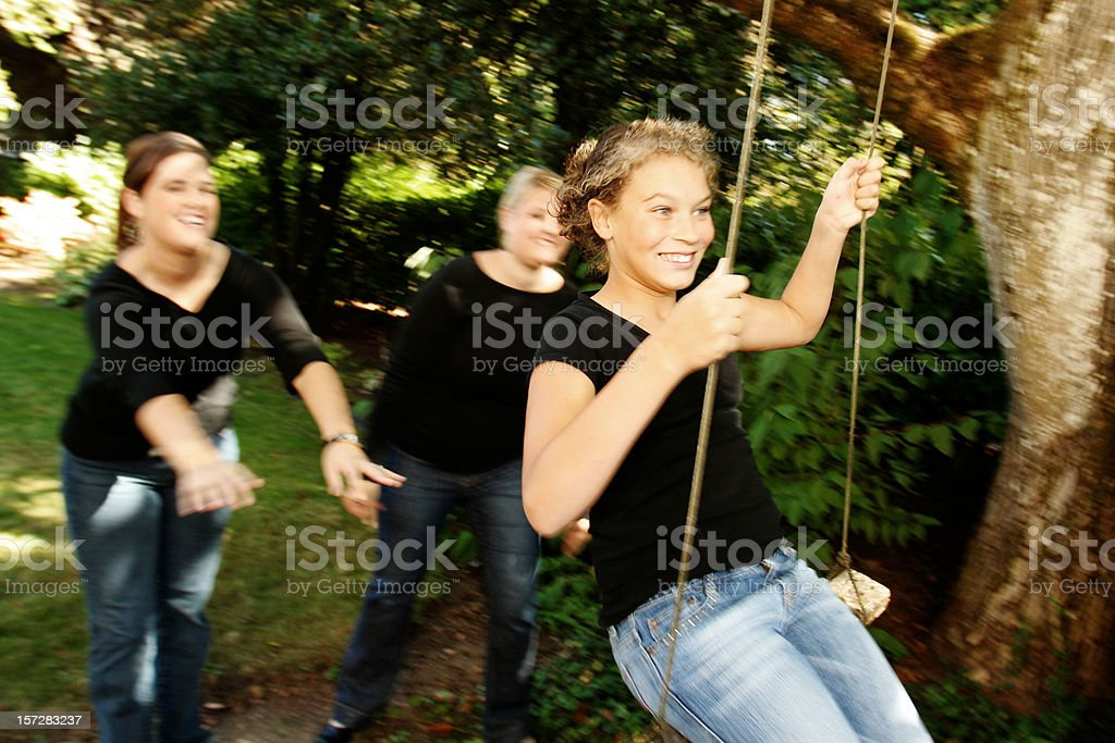 Sisters Pushing Each Other on a Swing royalty-free stock photo