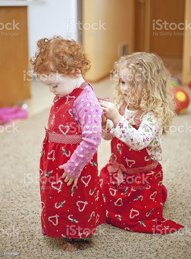 Sisters Putting on Red Aprons royalty-free stock photo