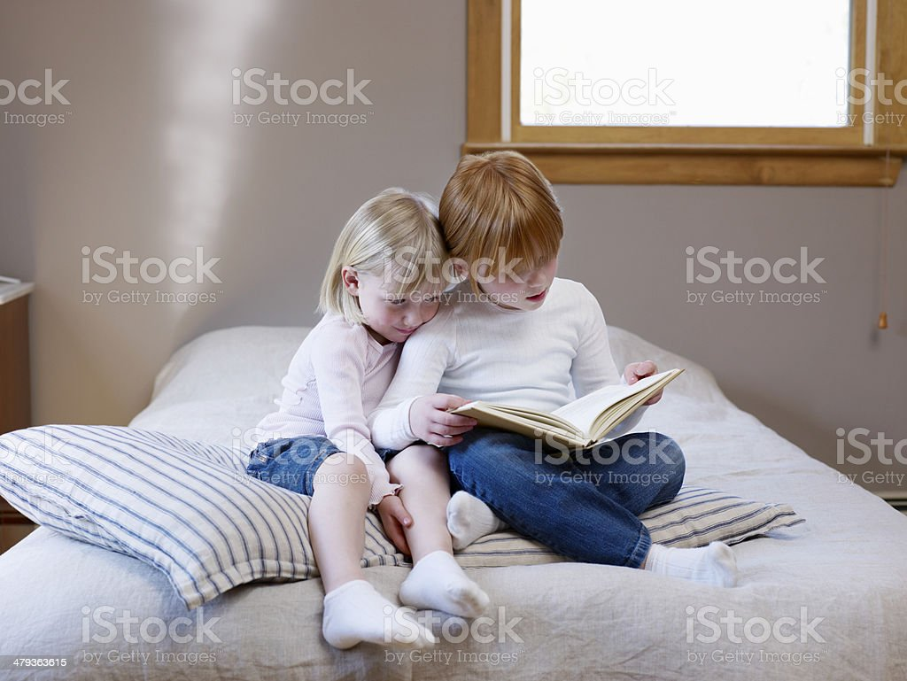 Sisters Reading Book On Bed royalty-free stock photo