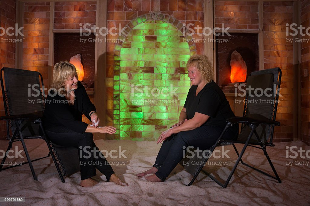Sisters rub sand on arms during halotherapy stock photo
