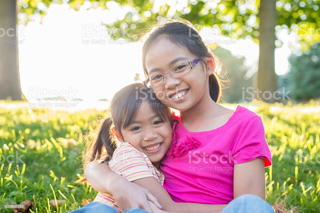 Sisters Sitting in the Grass stock photo