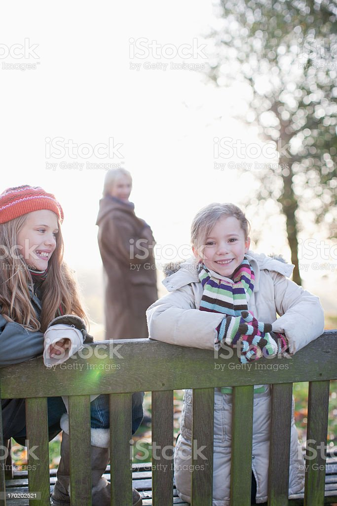 Sisters sitting on bench outdoors in autumn royalty-free stock photo
