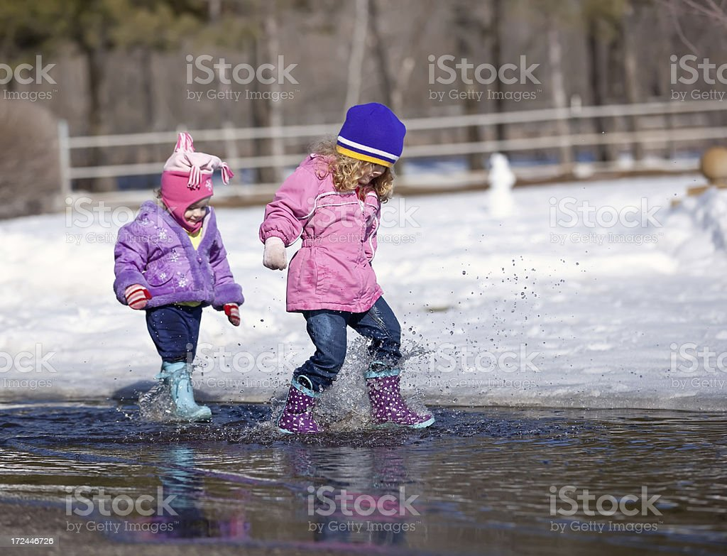 Sisters Splashing in Water Puddle royalty-free stock photo