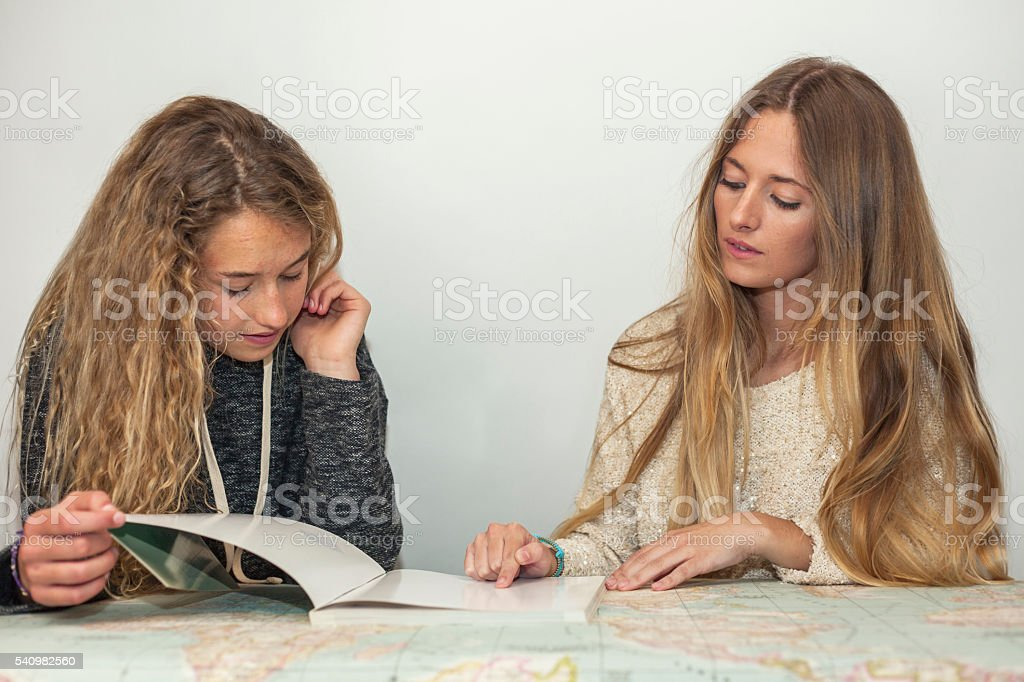 Sisters studying and doing homework over a table map stock photo
