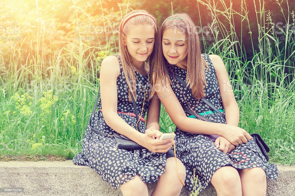 Sisters texting on smartphone among nature stock photo