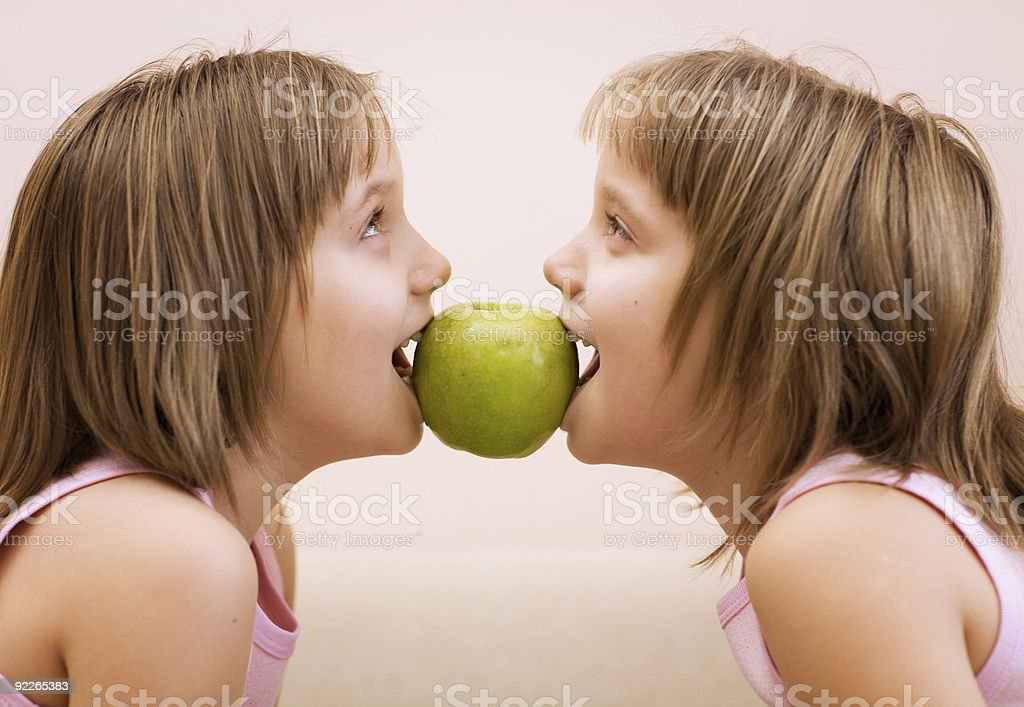 Sisters - twins with an apple royalty-free stock photo