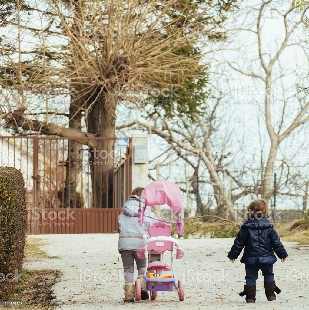Sisters walking side by side and pushing a tricycle stock photo