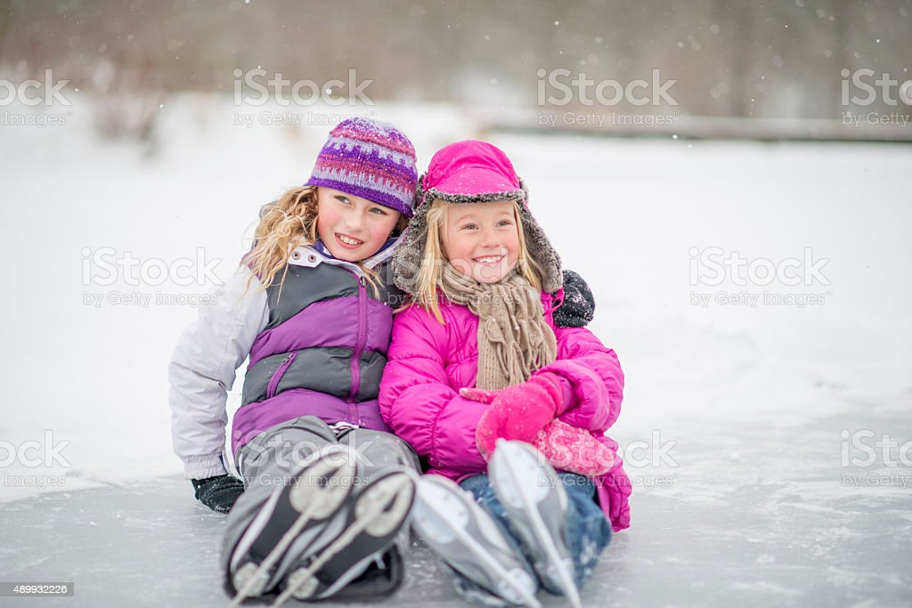 Sisters Wearing Ice Skates stock photo