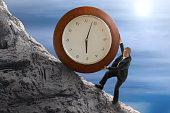 Sisyphus stressed for time man rolling huge clock up hill