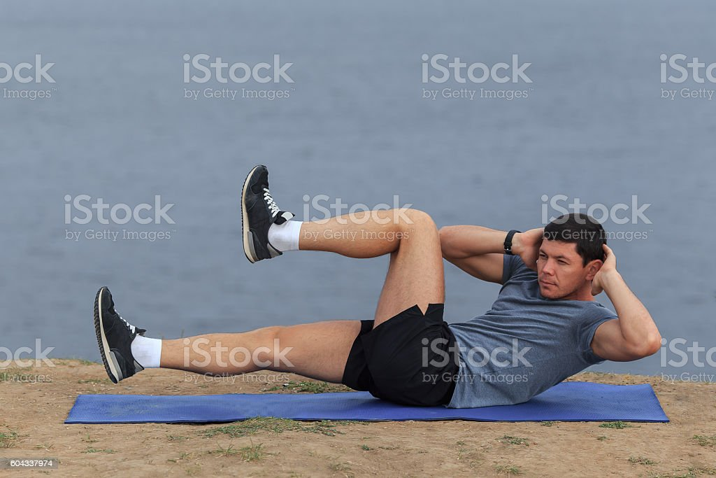 Sit ups - fitness man exercising sit up outside stock photo
