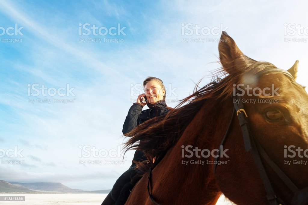 Sitting astride her horse, smiling woman talks on her cellphone stock photo