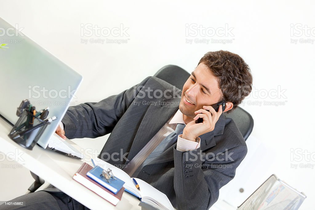 Sitting at office desk smiling modern businessman talking on mobile royalty-free stock photo
