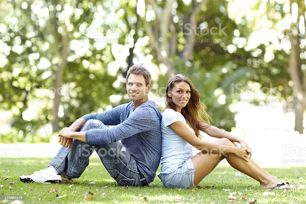 Sitting back-to-back in the park royalty-free stock photo