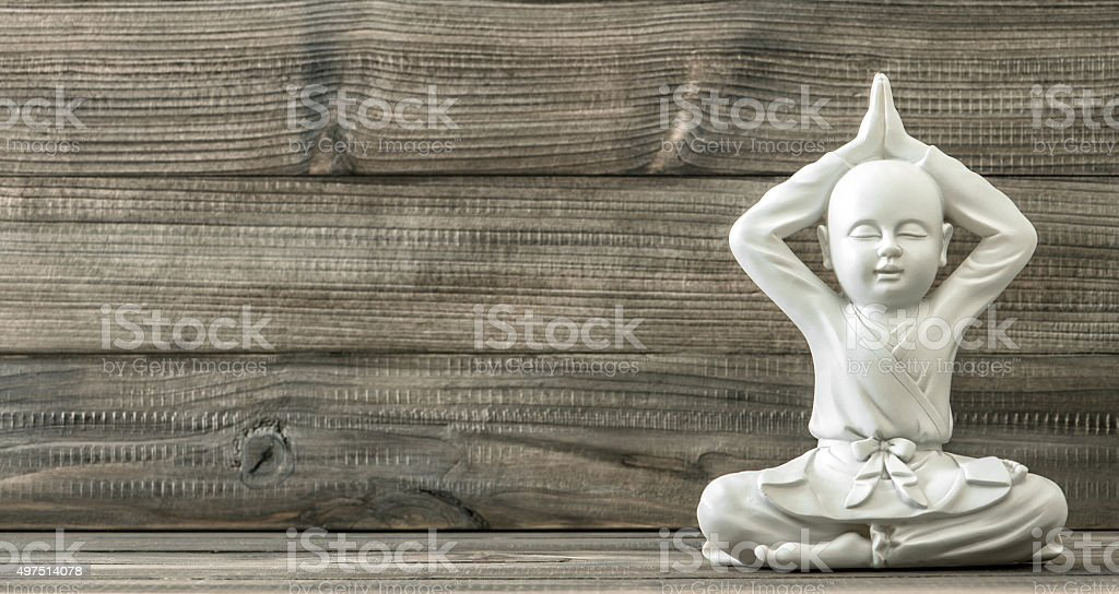 Sitting buddha. White monk statue on wooden background stock photo