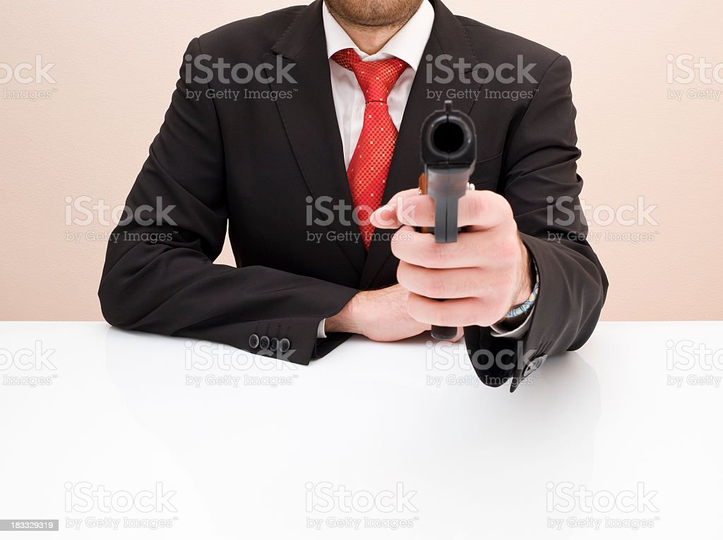 Sitting Businessman Holding A Gun To You royalty-free stock photo