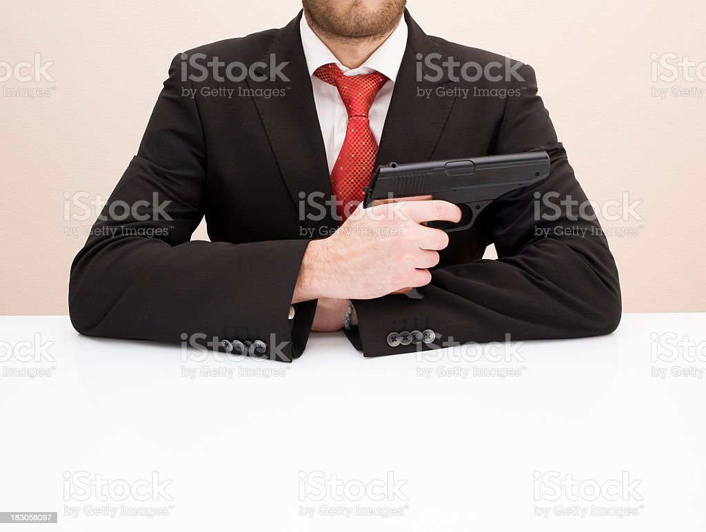 Sitting Businessman With A Gun In Hand royalty-free stock photo