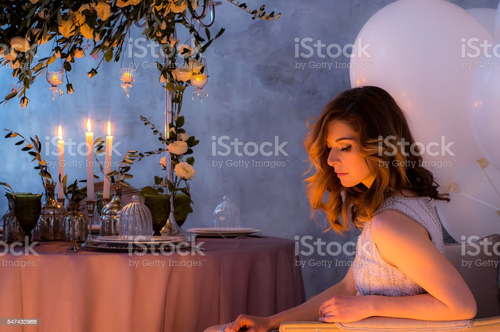 Sitting by the table bride with wedding decorations stock photo