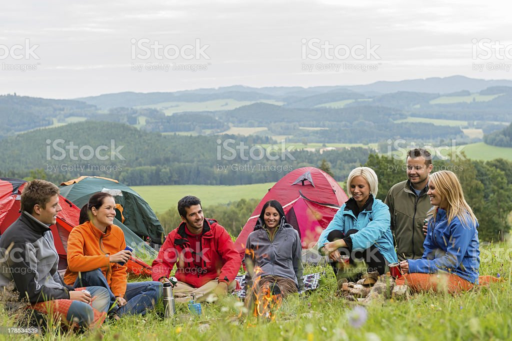 Sitting camping friends with tents and landscape royalty-free stock photo