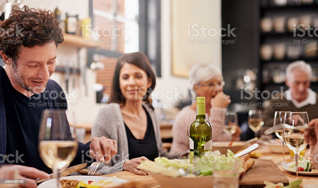 Sitting down to family dinner stock photo