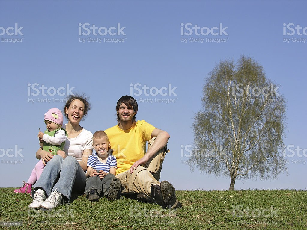 sitting family with two children. spring. royalty-free stock photo