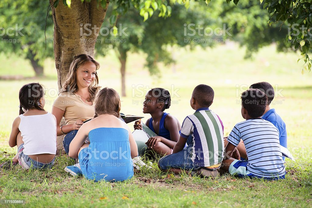 Sitting female teacher surrounded by school-aged children stock photo