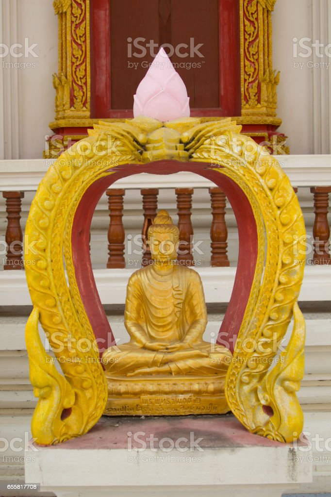 Sitting golden buddha statue in front of the church . stock photo