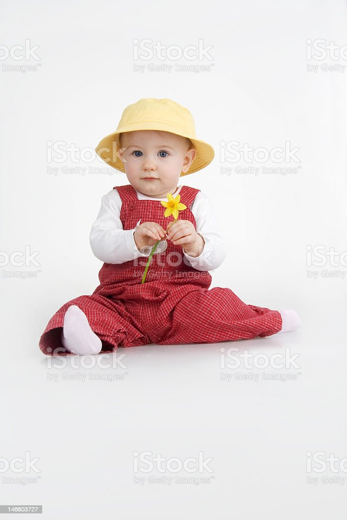 Sitting little girl in hat and with jonquil royalty-free stock photo