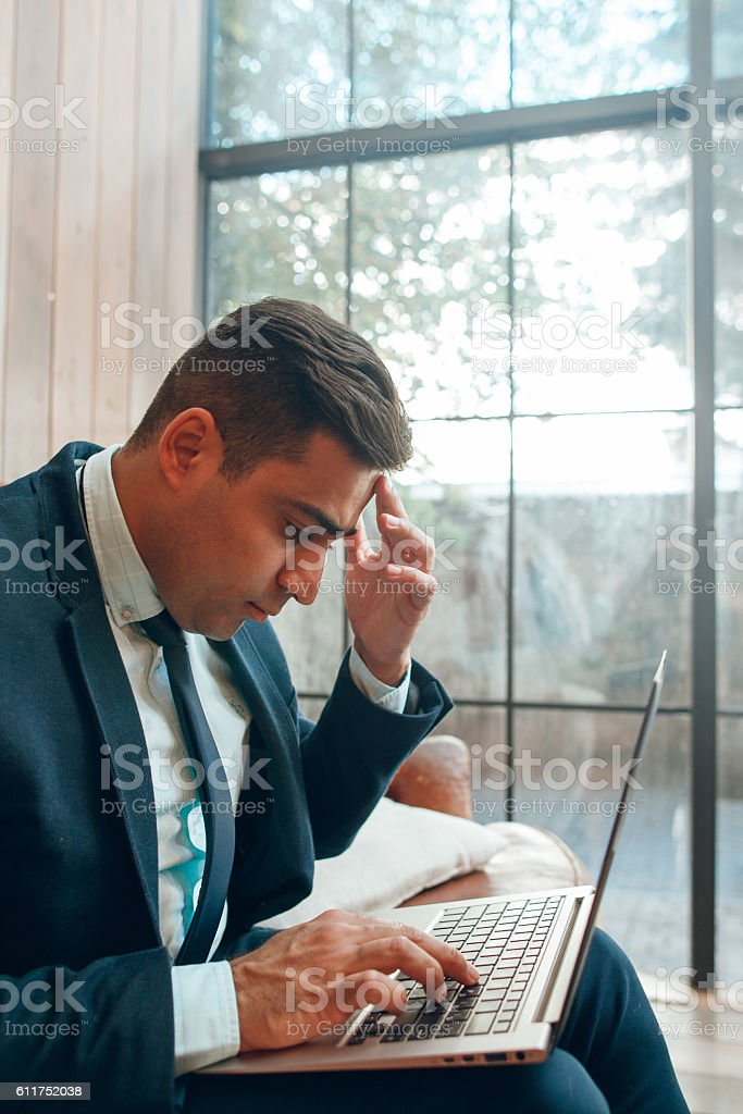 Sitting man looking at laptop screen stock photo