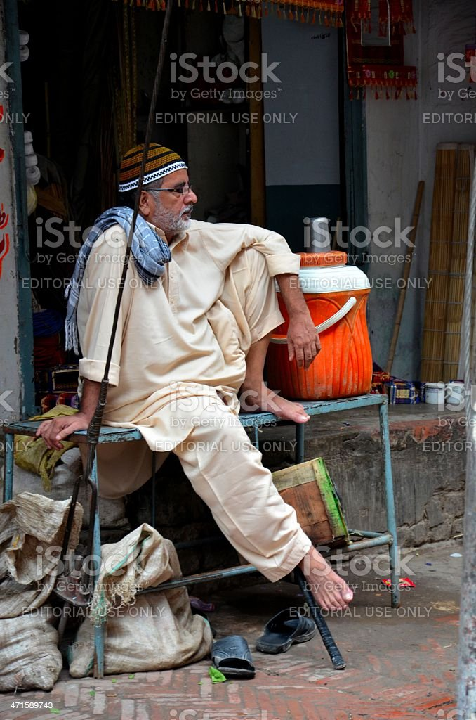 Sitting man relaxes inside Lahore walled city, Pakistan royalty-free stock photo