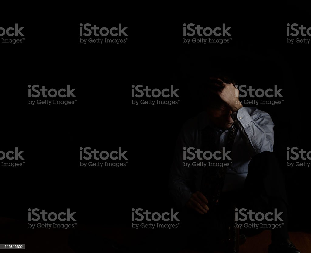 Sitting mature man holding head while holding beer stock photo