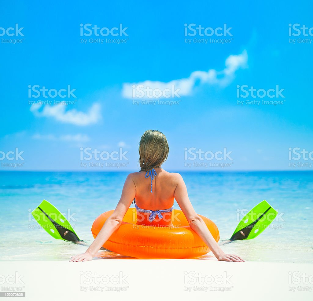 Sitting near the ocean in fins and lifebuoy stock photo