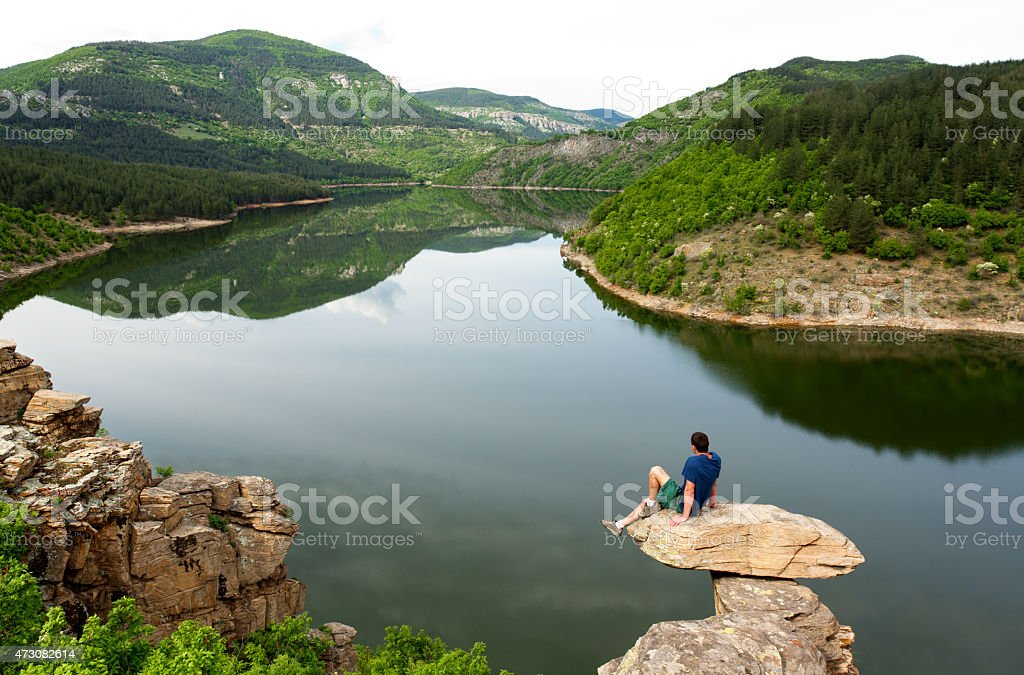 Sitting on a rock high above the water stock photo