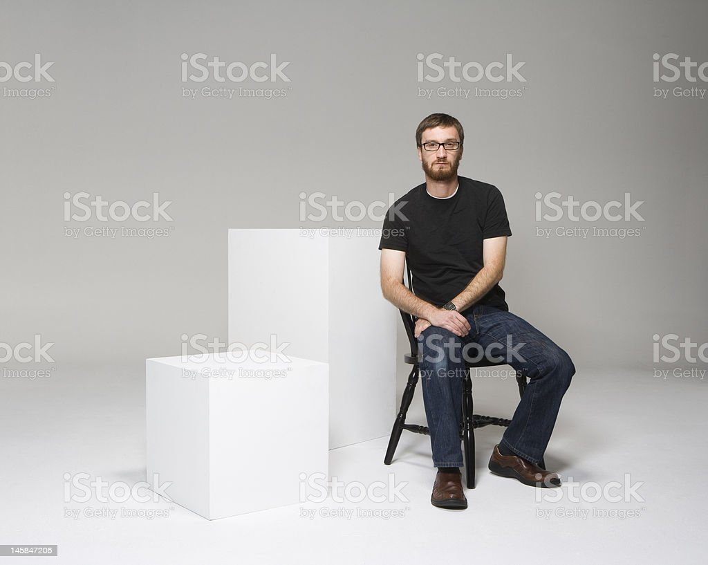 sitting on black chair with white cubes royalty-free stock photo