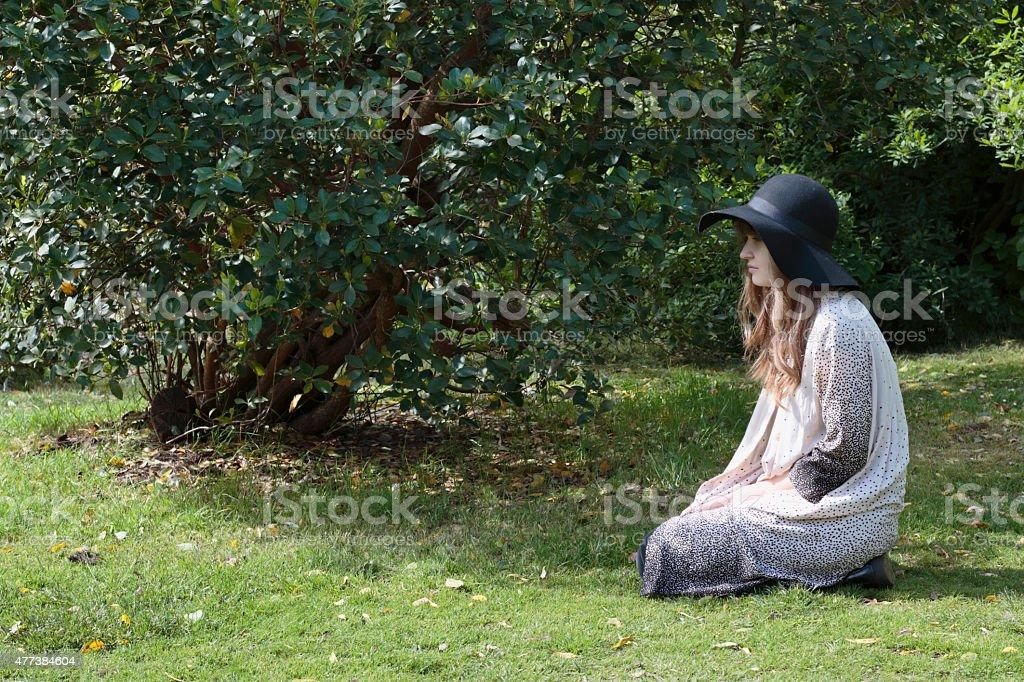Sitting on her heels Latvian tree girl outdoors stock photo