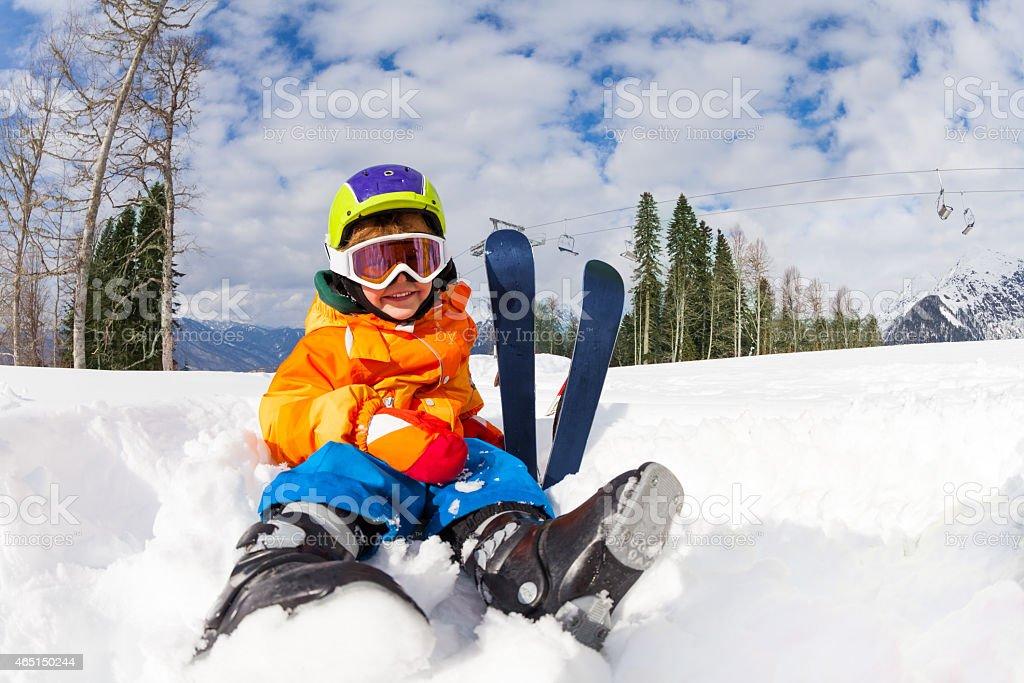 Sitting on snow boy in ski mask and helmet stock photo