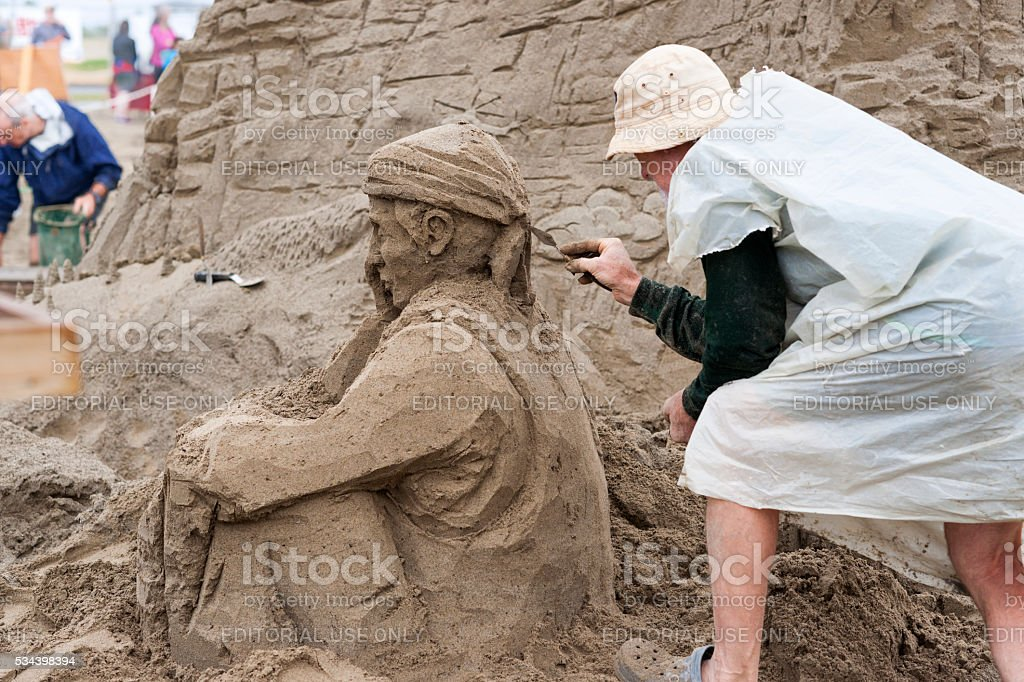 Sitting soldier sand sculpture stock photo