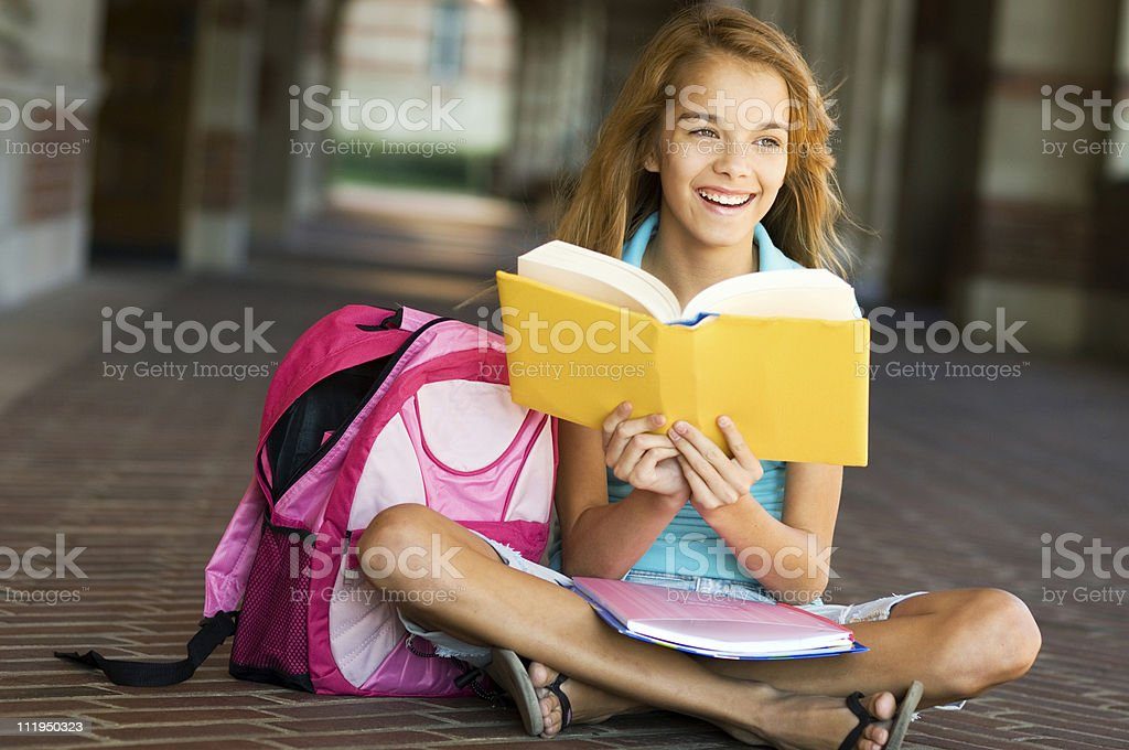 Sitting Teenage Schoolgirl Laughs while studying with books and backpack royalty-free stock photo