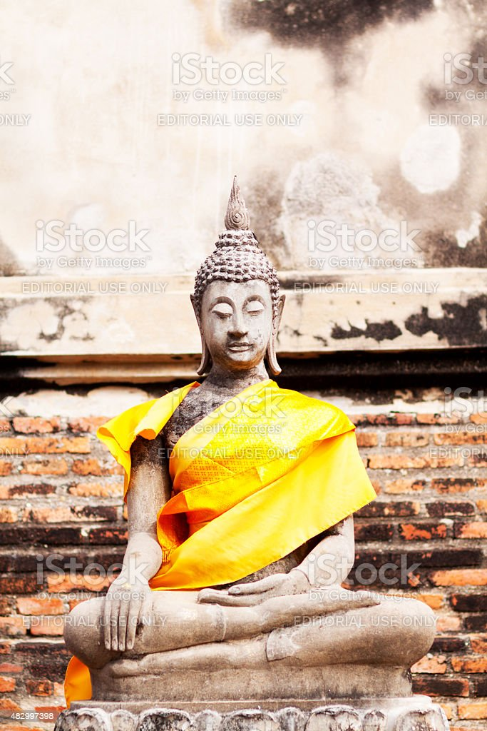 Sitting thai buddha with yellow scarf stock photo
