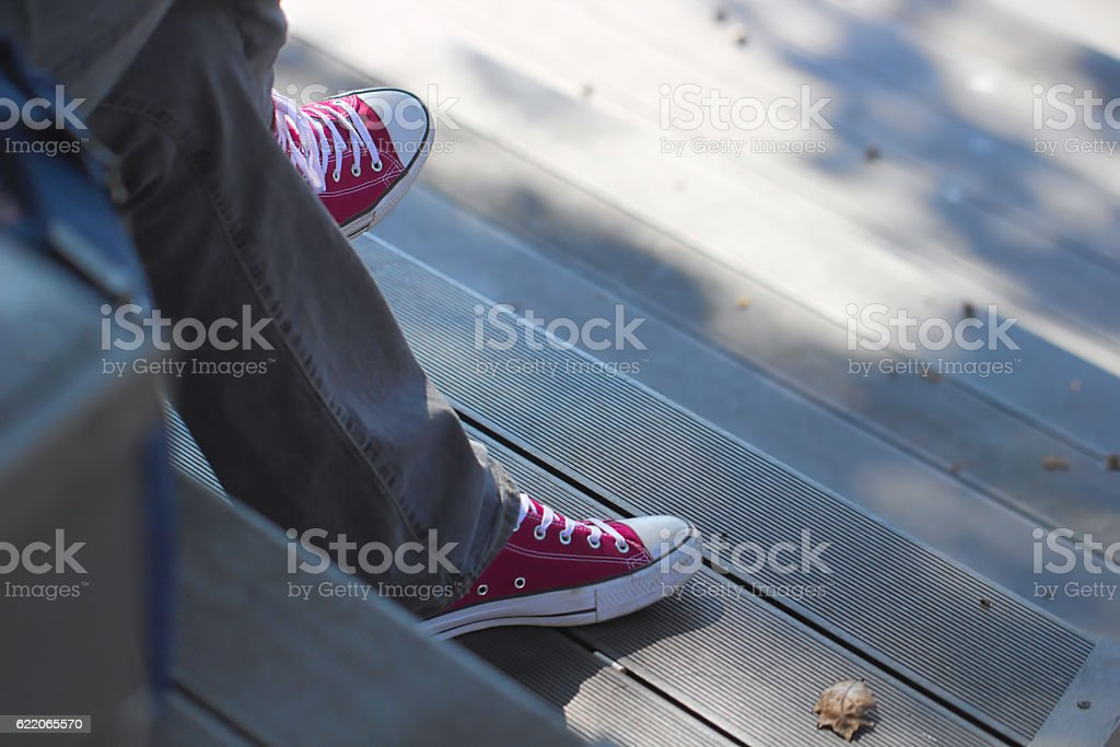 Sitting, waiting, wearing jeans red sneakers stock photo
