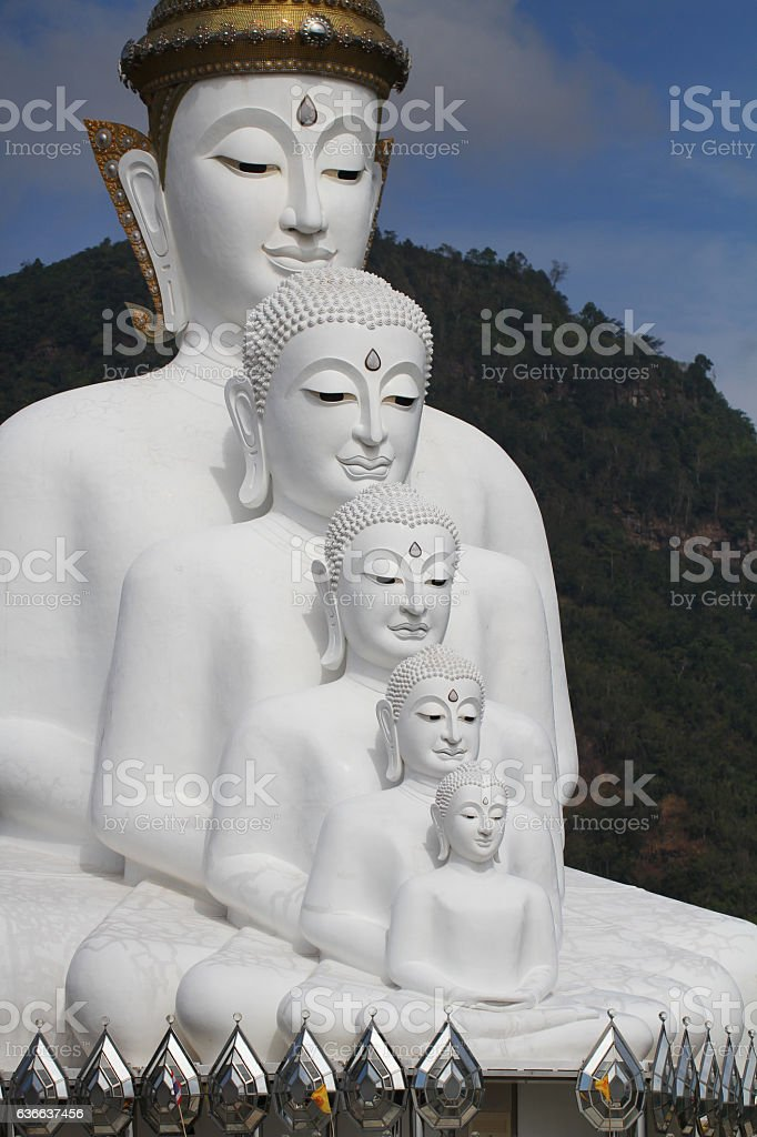 sitting white buddha statue well alignment in front of mountain stock photo