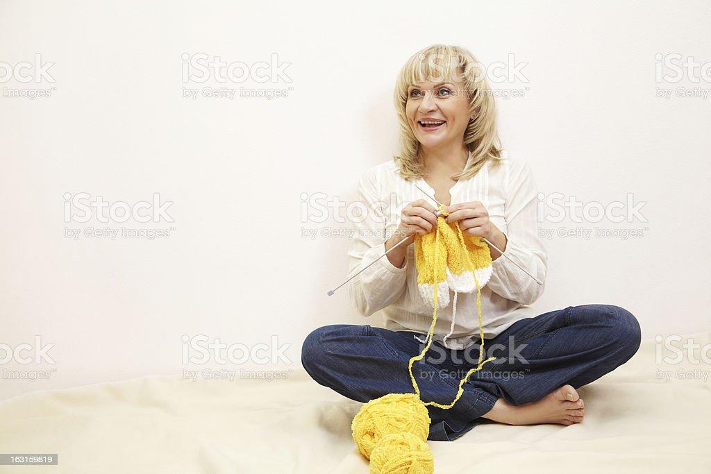 sitting woman knits stock photo