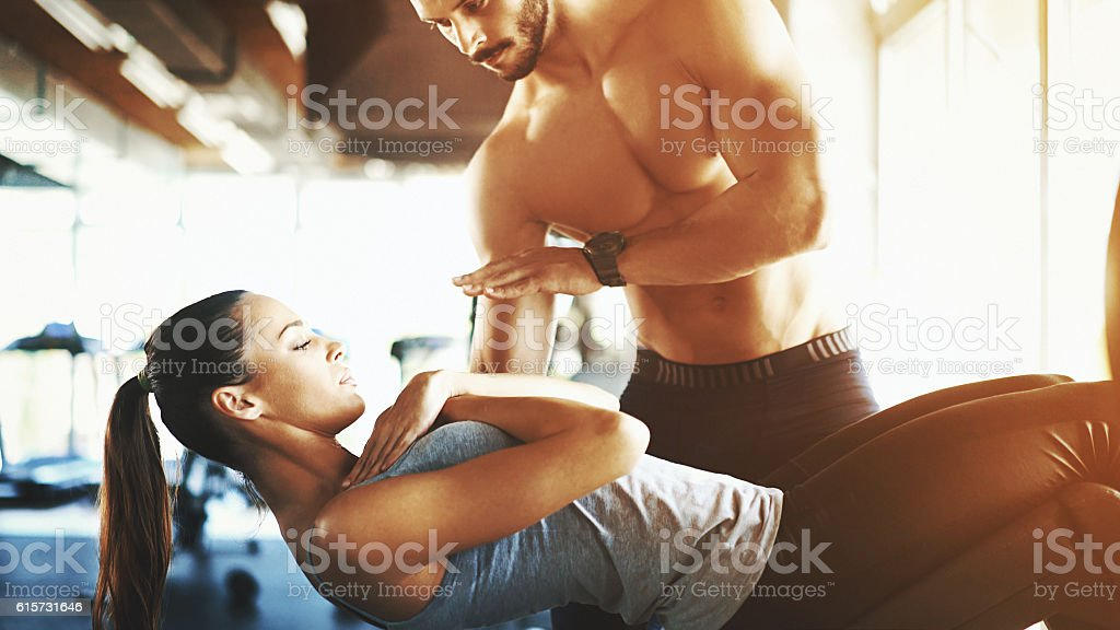 Situps exercise with coach assistance stock photo