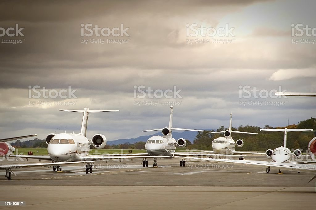 Six aircrafts lined up on tarmac on an overcast day stock photo