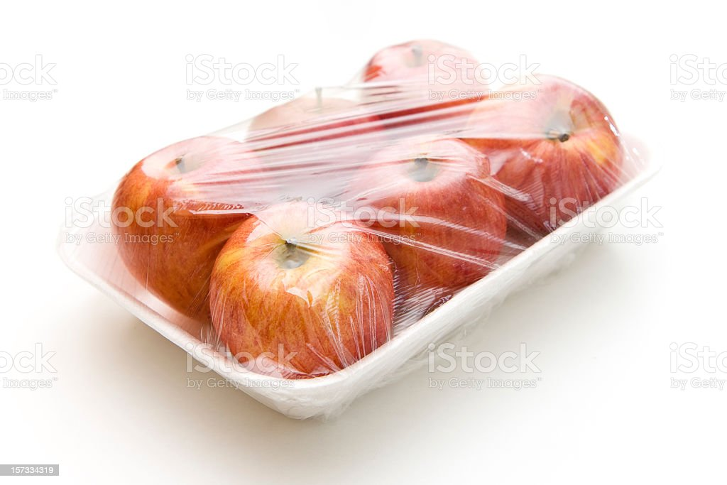 Six apples cling wrapped to a Styrofoam tray royalty-free stock photo