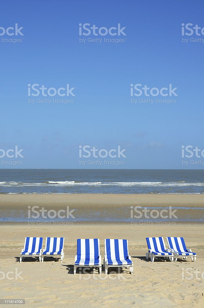 Six beach chairs in front of water line royalty-free stock photo